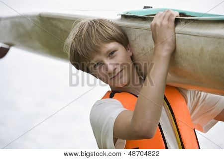 Closeup portrait of a teenage boy carrying kayak