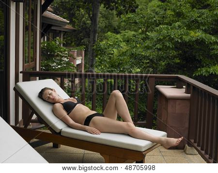 Full length of a young woman in bikini reclining on deckchair