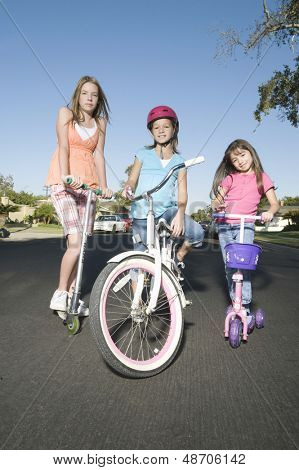 Full length portrait of children with scooters and bicycle