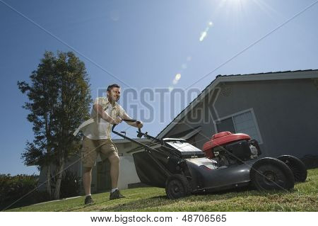Low angle view of a smiling man moving lawn