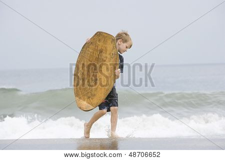 Full length side view of a little boy carrying a bodyboard in sea