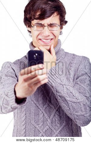 Young man taking picture of something strange on his mobile phone. Isolated on white background, mask included