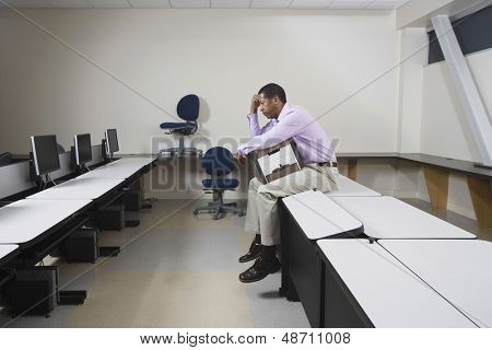 Full length side view of a depressed man sitting on desk with moving box