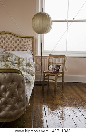 Chair and circular lampshade besides a cropped bed in bedroom