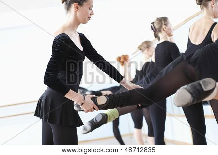 Ballet teacher adjusting foot positions of ballerinas at the barre