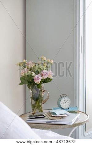Roses in vase on bedside table with books and alarm clock in bedroom