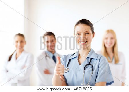 healthcare and medical concept - female doctor with group of medics showing thumbs up