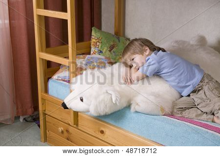 Thoughtful young boy with polar bear soft toy lying on bunk bed