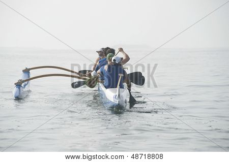 Rear view of multiethnic outrigger canoeing team on water