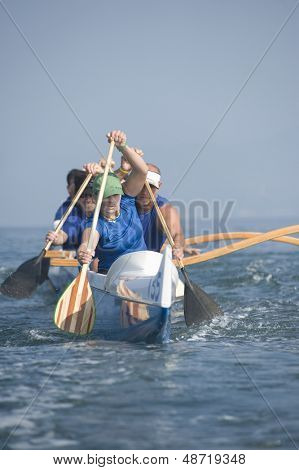 Multiethnic outrigger canoeing team paddling canoe in race