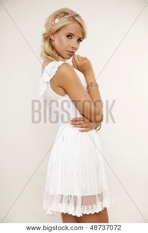 portrait of a beautiful young adult sensuality blonde babe girl in white elegance dress and flowers in hair isolated on light background
