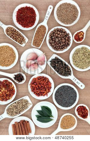 Large spice and herb selection in white china bowls and measuring spoons with millilitre measurement over papyrus background.