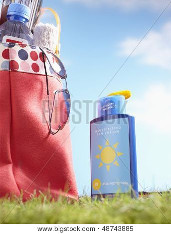 Bottle of suntan lotion and bag with beach items in grass close-up