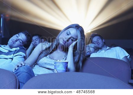 Group of young people sleeping while watching movie in the theatre