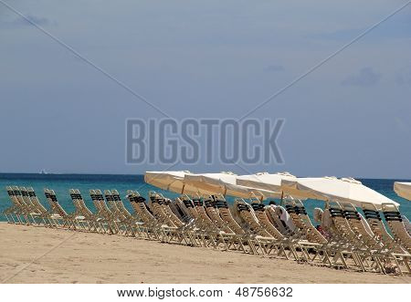 Line of empty lounge chairs on the sandy beach