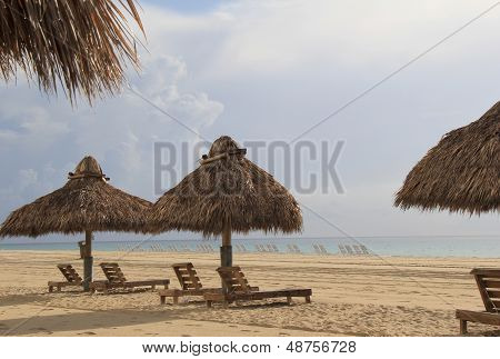 Hot sandy beach with tiki huts and lounge chairs