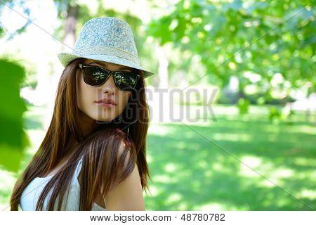 retrato ao ar livre linda mocinha, garota em parque de verão no fedora com marrom longo e óculos de sol
