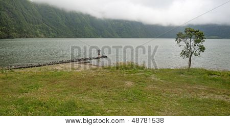 Man fishing in the lake of a volcanic crater