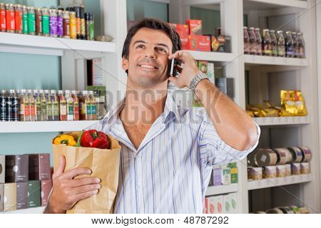 Happy mid adult man with vegetables in paper bag using cellphone in supermarket