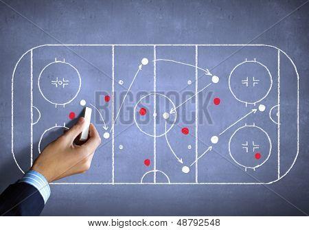 Close up image of human hand drawing hockey tactic plan