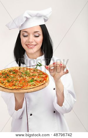 Beautiful girl chief-cooker with pizza isolated on white