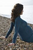 image of herne bay beach  - Side view of a young pregnant woman sitting on pebble beach - JPG