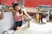 stock photo of diners  - Beautiful young woman with milkshake at the diner table - JPG