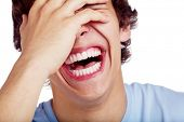 stock photo of laugh out loud  - Close up portrait of hard laughing young man - JPG