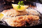 foto of wieners  - wiener schnitzel frying in a pan with lemon  - JPG