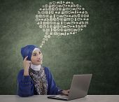 stock photo of muslimah  - Female muslimah thinking on abstract cloud in class - JPG