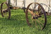 stock photo of stagecoach  - Side view of 2 metal wagon wheels from an old stagecoach from the 1800s - JPG