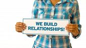 pic of courtesy  - A woman holding a We Build Realationships sign - JPG