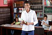 foto of librarian  - Portrait of happy female librarian holding books while standing in library with students studying in background - JPG