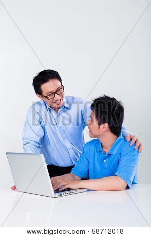 Chinese father helps his son with knowledge and experience for his complex and complicated homework assignments for the next day at school