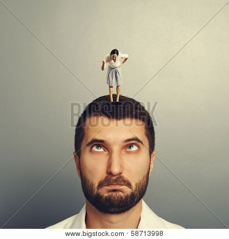 angry woman screaming at stupid man over grey background