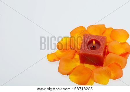 Spilt petals of the orange-rose around the aromatic candle