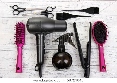 Hairdressing tools on white wooden table close-up