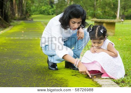 Indian family outdoor activity. Candid portrait of mother and daughter exploring on nature, outdoors education.