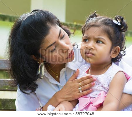 Indian family outdoor. Modern mother is comforting her crying daughter.