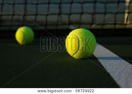 Tennis Balls on the Court Close up with the Net Beyond