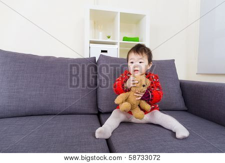 Little girl playing doll at home