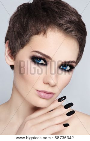 Portrait of young beautiful woman with stylish short haircut and smokey eyes