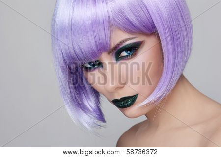 Portrait of young beautiful woman with fancy green make-up and violet wig