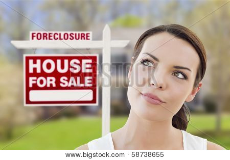 Thoughtful Pretty Mixed Race Woman In Front of Home and Foreclosure House For Sale Real Estate Sign Looking Up and to the Side.