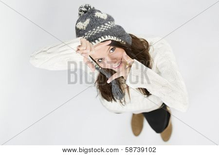 Cute joyful girl in white winter sweater and grey cap, making a photo frame with her hands while looking up, isolated on grey background.