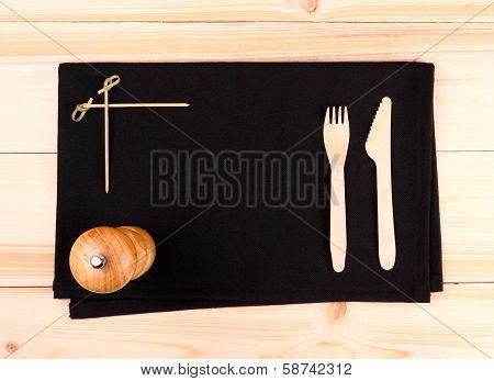 Wood Cutlery On Black Placemat As Menu Board