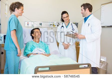 Young doctors discussing notes while happy patient and nurse looking at them in hospital room