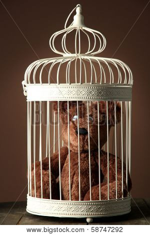 Toy bear in decorative cage on wooden table, on brown background