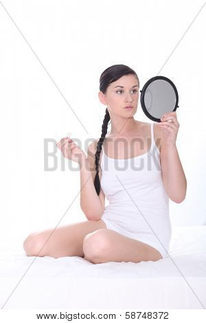 Young woman sat on bed holding mirror