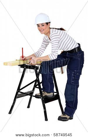 Tradeswoman marking a measurement on a wooden plank